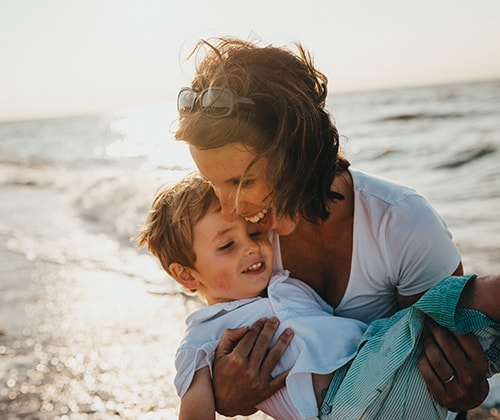 expert breast care image of woman on beach with young boy